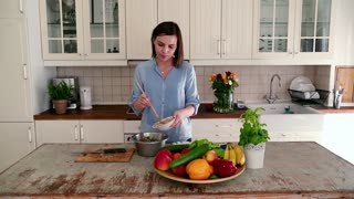 Portrait of beautiful woman mixing salad and talking to the camera