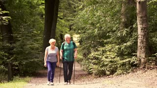 Portrait of happy, mature couple hiking in forest