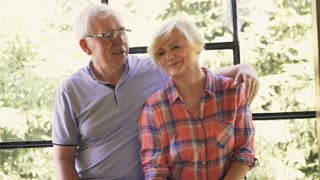 Portrait of happy, mature couple sitting by window at home