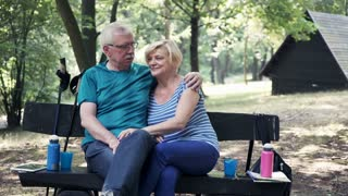 Portrait of happy, mature couple sitting in bench park
