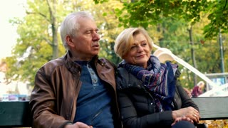 Portrait of happy, mature couple sitting on a bench in the city park