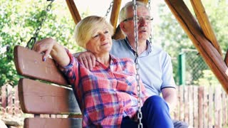 Portrait of happy, mature couple sitting on the swing in the garden