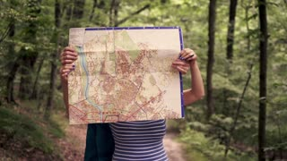 Portrait of happy, mature couple standing with map in the forest