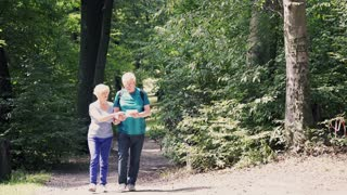Portrait of happy, mature couple with tablet walking in the park