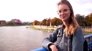 Portrait of happy teen girl standing on the bridge with symbol of lock love
