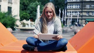Portrait of happy woman with tablet computer sitting in the city