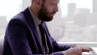 Portrait of sad, unhappy businessman sitting by table in the office