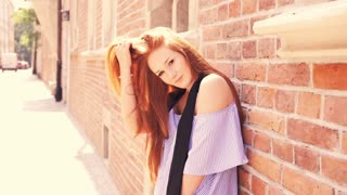 Portrait of young beautiful woman with red hair standing by brick wall in the city