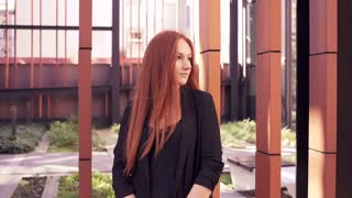 Portrait of young happy woman with red hair in the city