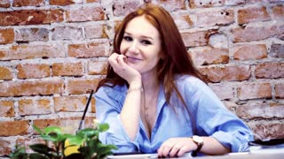 Portrait woman of young beautiful woman with red hair in cafe