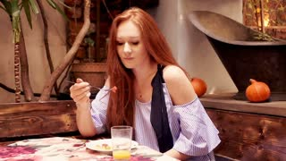 Portrait woman of young beautiful woman with red hair in vegetarian cafe