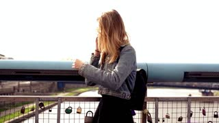 Pretty, happy teen girl talking on cellphone on the bridge with symbol of lock love