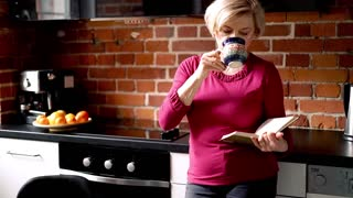 Pretty, senior woman reading book in the kitchen
