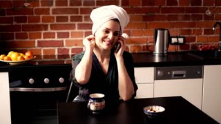 Pretty woman in bathrobe and turban talking on cellphone and drinking coffee in kitchen in the morning