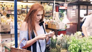 Pretty woman with red hair choosing delicious vegetables at local farmers market