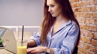 Pretty woman with red hair finish work on laptop and relax in cafe