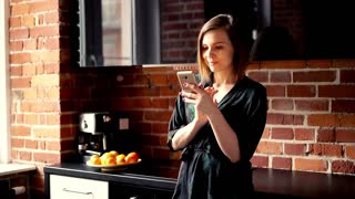 Pretty, young  woman standing with smartphone in the kitchen