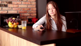 Pretty, young woman watching TV by table at home