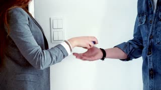 Real estate agent giving client keys to his new home, focus on hands