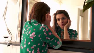 Sad, beautiful woman standing in front of the mirror