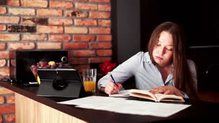 Sad, overwhelmed student doing notes and learning by table at home