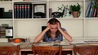 Sad, overwhelmed student sitting with books by table at home