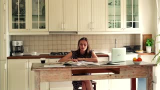 Sad, overwhelmed student sitting with books by table in the kitchen