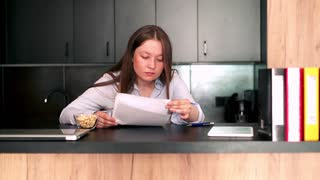 Sad, overwhelmed woman reading documents by table