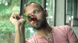 Sad, pensive man smelling rose by the window at home