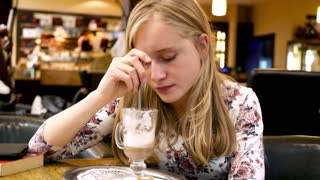 Sad, pensive woman sitting with coffee in cafe