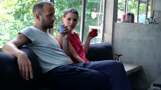 Sad, serious couple talking and drinking beverages sitting at home, 4K