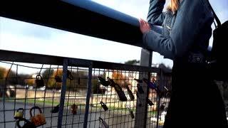 Sad teen girl standing on the bridge with symbol of lock love