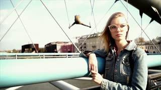 Sad teen girl standing on the bridge.