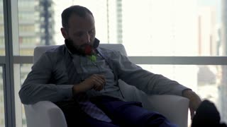 Sad, unhappy bussinesman sitting on armchair with red rose
