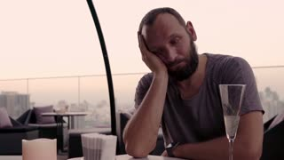 Sad, unhappy man drinking alcohol on roof bar