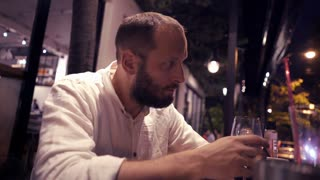 Sad, unhappy man drinking wine sitting in cafe during evening, 4K