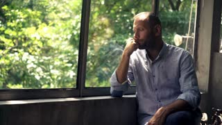 Sad, unhappy man looking by window at home, 4K