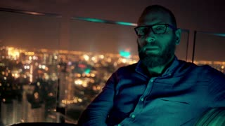 Sad, unhappy man waiting for someone in skybar during night, 4K