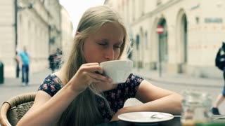 Sad, unhappy woman drinking coffee in cafe