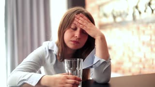 Sad woman having headache by table at home