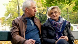 Senior couple having relationship difficulties on a bench park