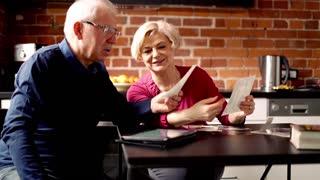 Senior couple looking photos in the kitchen