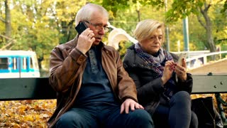 Senior couple talking on cellphone in the city park