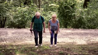 Senior couple walking in the park, woman is tired