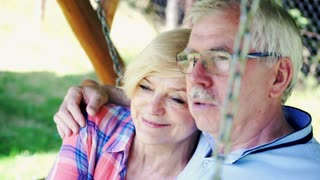 Senior, happy couple kissing on the swing in the garden
