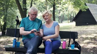 Senior, happy couple listening to music on cellphone on bench park