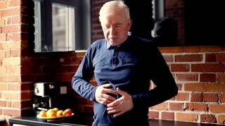 Senior man gets stomach ache standing in the kitchen