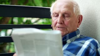Senior man has problems with vision while reading newspaper on the balcony