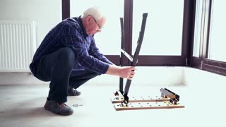 Senior man matching pieces of furniture on floor at home