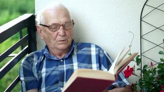 Senior man reading book on the balcony